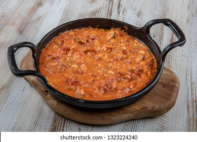 Menemen Turkish breakfast food egg, tomatoes and pepper in pan with concept background.