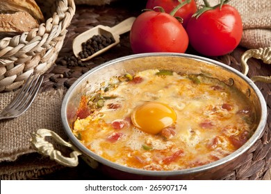 Menemen Turkish breakfast food egg, tomatoes and pepper in pan with concept background