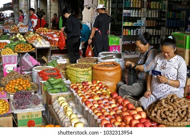 MENGHAI, YUNNAN, CHINA, APRIL 19, 2009. Two women in an outdoor market sell fruit and spices outside a shop selling toiletries and cosmetics, while customers buy fruit from the adjacent vendor.