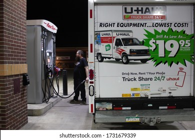 Menomonee Falls, WI / USA - May 3, 2020: A millennial man fills up his U-Haul truck with gas in the middle of the night at a Kwik Trip station.