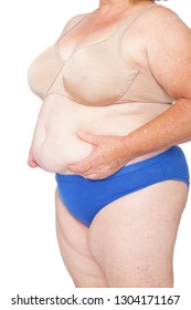 Menopausal woman with weight gain after brachioplasty, panniculectomy, abdominoplasty and mummy makeover. 45 degree view left, hands holding excess abdominal weight, copy space. Makeover inspiration.