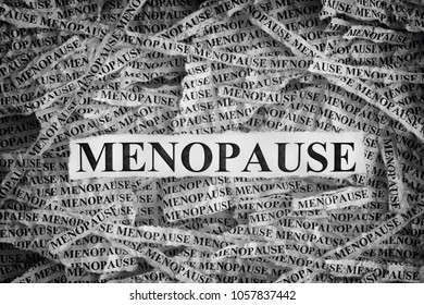 Menopause. Torn pieces of paper with the word Menopause. Concept Image. Black and White. Closeup.