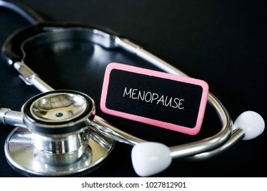 MENOPAUSE word on patient tag in black background. Medical and healthcare concept.