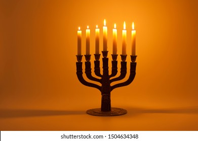 Menorah with 7 lighted candles isolated on golden background. Horizontal shot.