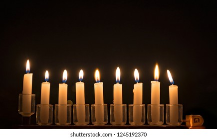 Menorah with burning candles is traditional symbol for Hebrew Holidays and celebration of Hanukkah. Background of night sky, selective focus on menorah