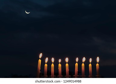 Menorah with burning candles is traditional symbol for Hebrew Holidays and celebration of Hanukkah. Background of night or dawn sky, selective focus on menorah