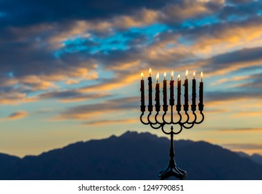 Menorah with burning candles is traditional symbol for Hebrew Holidays and celebration of Hanukkah. Background of night or dawn sky, selective focus on attributes of Hanukkah