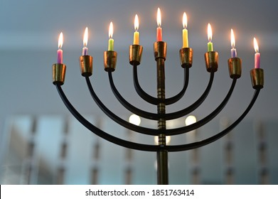 Menorah candelabra lit with eight candles on the last day of Hanukkah Jewish holiday.