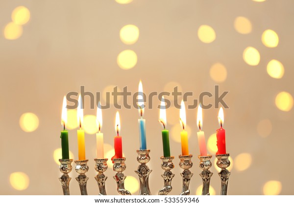 Menorah with candles for Hanukkah against defocused lights, close up