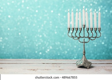 Menorah with candles for Hanukkah celebration over bokeh background