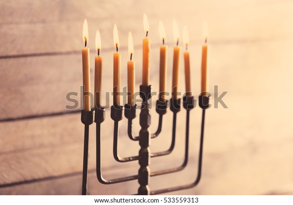Menorah with candles for Hanukkah on blurred wooden background, close up