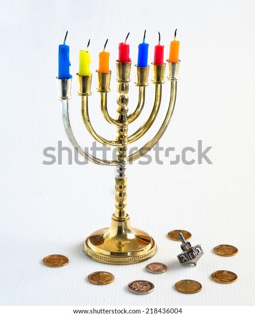 Menorah with candles, silver dreidel and Israelis coins for Hanukkah Celebration.
