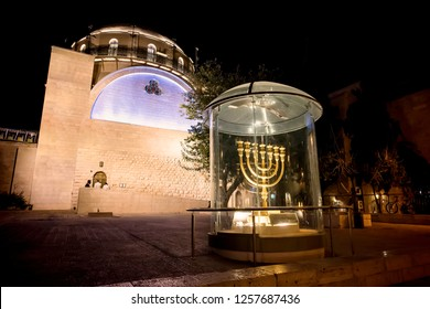 Menorah - the golden seven-barrel lamp - the national and religious Jewish emblem near the Dung Gates on the background of the synagogue Hurva at night in the Old City of Jerusalem, Israel
