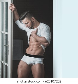 Men's abs press. Body after exercise. Man after the gym. Sexy guy in white underwear is standing near the door. Attractive sports man looking at his belly. Ideal perfect muscles and beautiful figure