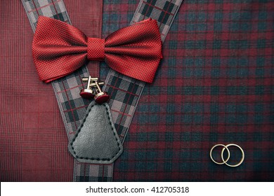 Men's accessories - bow tie, wedding rings, cufflinks on textile background.