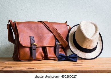 Men's accessories with brown leather bag, brown hat and blue bow tie on wooden table over wall background