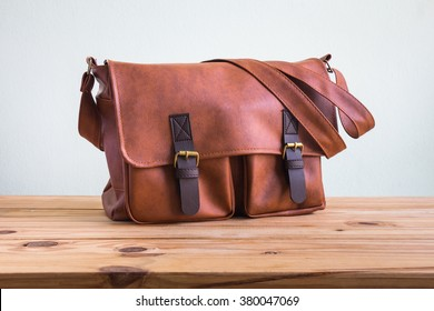 Men's accessories with brown leather bags on wooden table over wall background