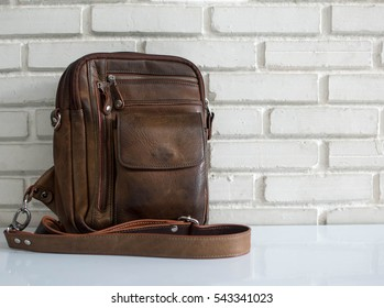 Men's accessories with brown leather bags on wooden table over wall background.