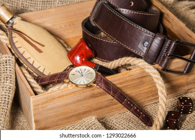 Men's accessories with brown leather belt, sunglasses, watch, smoking pipe and bottle with perfume on rustic background.