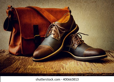Men's accessories with brown shoes, leather bag and belt on wooden table over grunge background, still life style