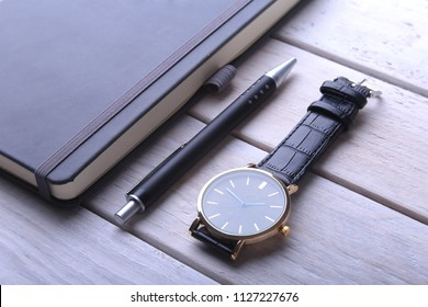 Men's accessories for business and rekreation. Leather notebook, watch and pen on wood background.. Top view composition.