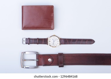 Men's accessories for business and rekreation. Leather belt, wallet, watch and smoking pipe on white background.. Top view composition.