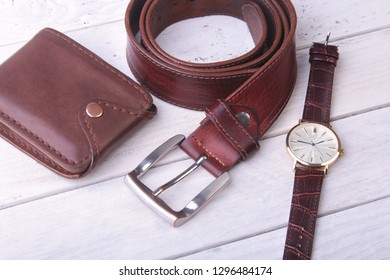 Men's accessories for business and rekreation. Leather belt, wallet, watch and smoking pipe on wood background.. Top view composition.