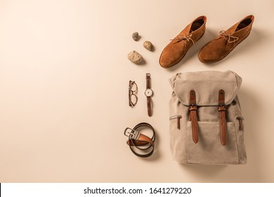 Men's accessories - camel suede desert shoes (boots), khaki backpack, leather belt, watch and glasses. Collection captured from above (top view, flat lay). Background layout with free copy space.