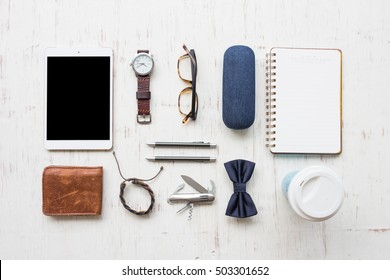 Men's accessories, coffee cup, stationary and white tablet on white wooden board background