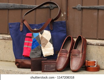Men's accessories in a pile making a scene featuring a leather bag, pair of shoes, belt and socks.