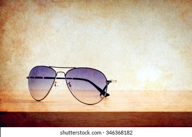 Men's accessories with sunglasses on wooden table over wall grunge background