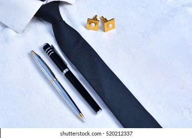 Men's accessories - tie, cufflinks, pencil and pen on a white shirt.