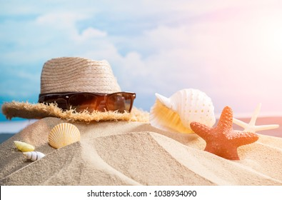 Men's accessories with vintage hat and sunglasses on exotic golden sea sand dunes,Summer holiday background, Straw hat with shells on beach,Vacation and travel items,Summer accessories on sandy beach,