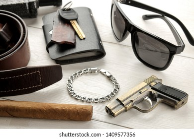 Men's Accessories.men's style. Glasses, business card holder, cigar, smartphone, notebook, headphones, and a pistol-lighter on a blue wooden background.