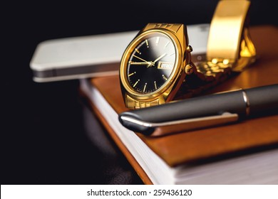 Men's accessory, golden watch, pen and mobile phone on the leather diary