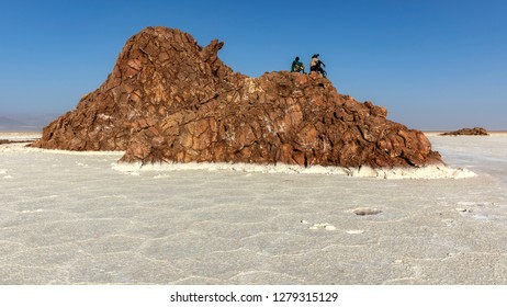 Mens armed with machine guns guard tourists while visiting the volcano and salt lake at Danakil depression, Ethiopia