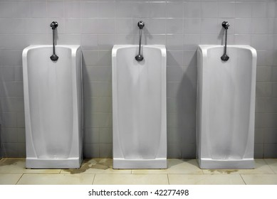 Mens bathroom urinals with stained floor.