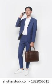 Herrliche Schönheit, Mode. Ansprechender junger Geschäftsmann mit Vollkörper, weißem Hemd und blauer Hose mit Turnschuhen mit HandHandtasche