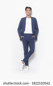 Herrliche Schönheit, Mode. Schöner ordentlicher junger Geschäftsmann mit weißem Hemd und blauer Hose mit Turnschuhen Händchen in Taschen, positiver Studioaufnahme