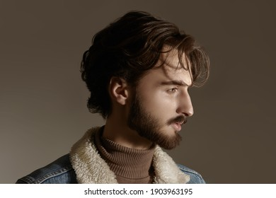 Men's beauty and hairstyle. Portrait of a handsome man with wavy dark hair and a beard on a gray background.