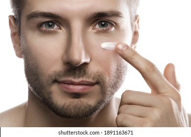 Men's beauty. Young man is applying moisturizing and anti aging cream on his face against white background