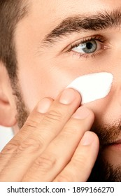Men's beauty - Young man is applying moisturizing and anti aging cream on his face against white background