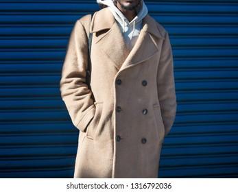 Men`s beige cashmere wool jacket on male model posing near blue wall in the city street