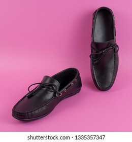 Men's black moccasins, loafers isolated on pink background. Side view, top view