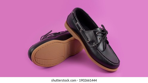Men's black moccasins, loafers isolated on pink background.