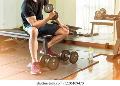 Men's black shirt are lifting dumbbells in the fitness.
