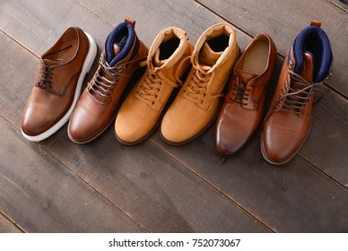 men's boots shoes with leather shoes on a wooden background.