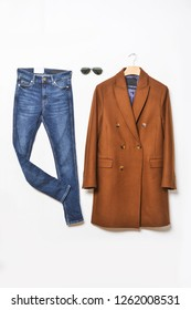 Men's brown coat on hanging with blue jeans and sunglasses