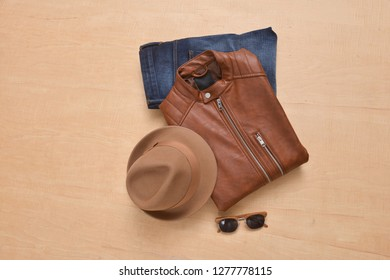 Men's brown leather jacket with blue jeans and sunglasses, hat-wooden background