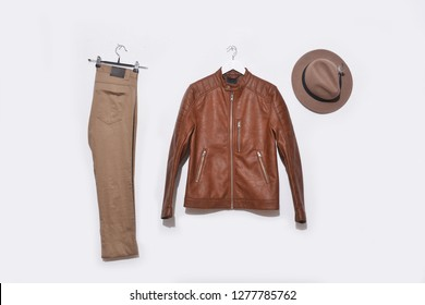 Men's brown leather jacket and pants and hat on hanging-wooden background